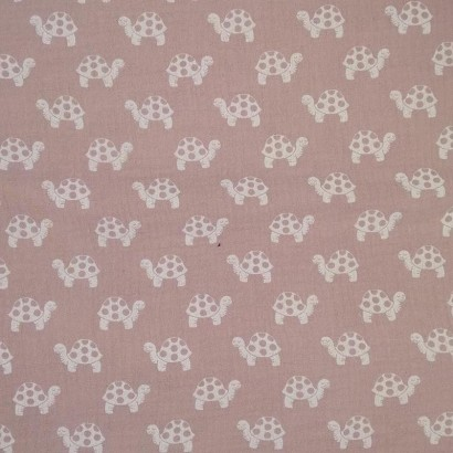 Tela de algodón rosa con tortugas blancas