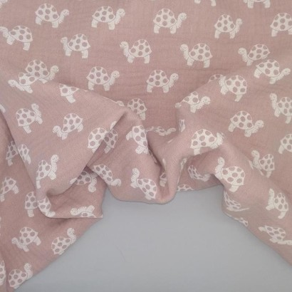 Tela de algodón rosa con tortugas blancas arrugada