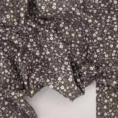 Tela de algodón flor blanca en fondo negro arrugada